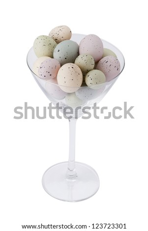 Vertical image of painted eggs with black specks placed inside a big martini glass - stock photo