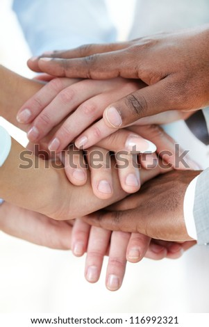 Vertical image of pile of hands of business partners - stock photo