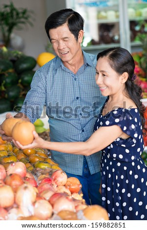 Vertical image of senior family couple choosing fresh fruits at the market on the foreground - stock photo