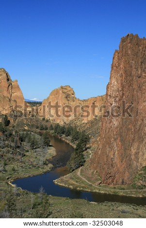 vertical image of the Crooked River curving past the cliffs of Smith Rock State Park - stock photo