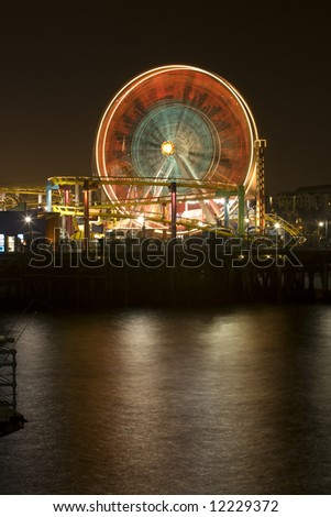 Vertical image of the famous Pacific Wheel at Santa Monica Pier in Southern California with a roller coaster ride in the foreground - stock photo