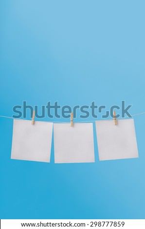 Vertical image of three squares of note paper for messages, pegged to hang on washing line against a blue sky.  Left blank to provide copy space for notices. - stock photo