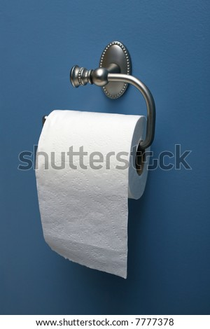 vertical image of toilet paper on roller on blue wall - stock photo