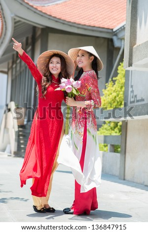 Vertical image of two girls wearing in national clothing outdoors