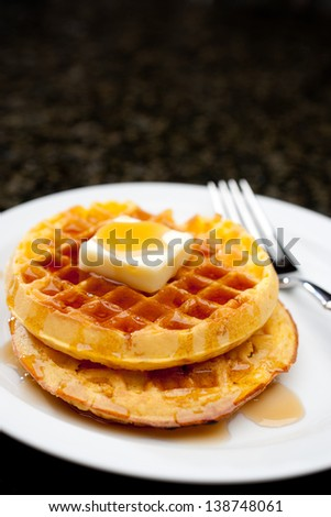 Vertical image of waffles covered in maple syrup - stock photo