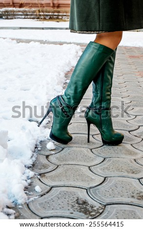 Vertical image of women in high boots in winter and copyspace - stock photo
