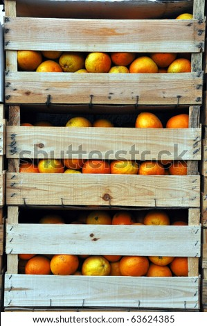 Vertical image of wooden crates with oranges. - stock photo