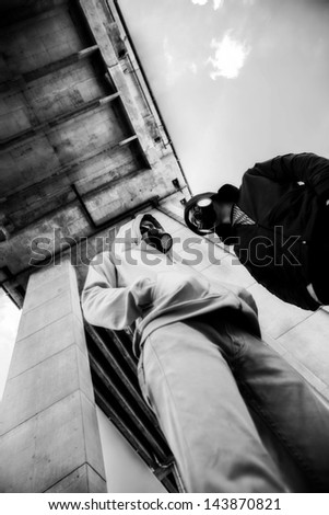 Vertical image of young guys in gas-masks standing outside - stock photo