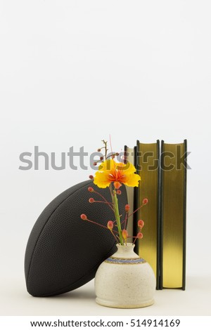 Vertical image with copy space is football with books and bird of paradise flower in vase reflects commitment of scholar athletes.  Symbols of athletics and education balanced in achievement.
