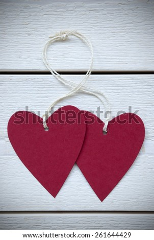 Vertical Image With Two Empty Red Hearts Label With White Ribbon On White Wooden Background With Copy Space Your Text Here Or Free Text For Advertisement Vintage Retro Or Rustic Style With Frame - stock photo