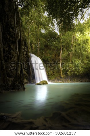 Vertical nature background of tropical waterfall in jungle forest with warm sunlight shines through trees and leaves  - stock photo