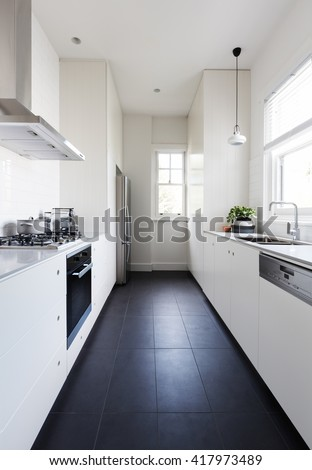 Vertical of a long galley style monochrome newly renovated kitchen - stock photo