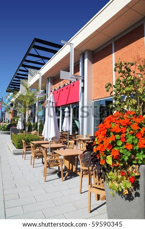 Vertical of an inviting modern sidewalk cafe restaurant on a bright sunny day. - stock photo