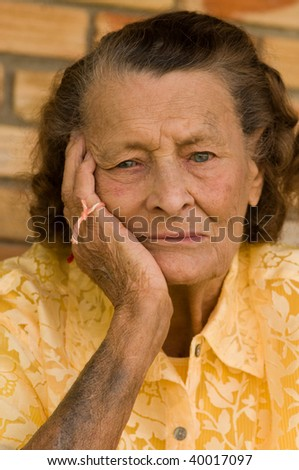 vertical of senior caucasian woman with head in hand and string on fingers wondering what she forget - stock photo