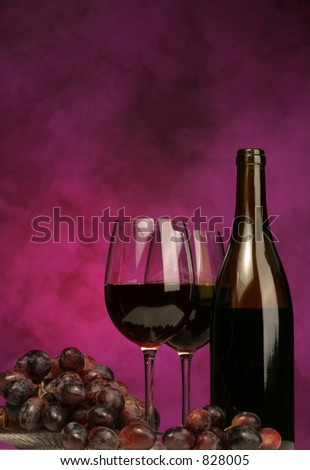 Vertical of Wine bottle with glasses and grapes on purple background - stock photo