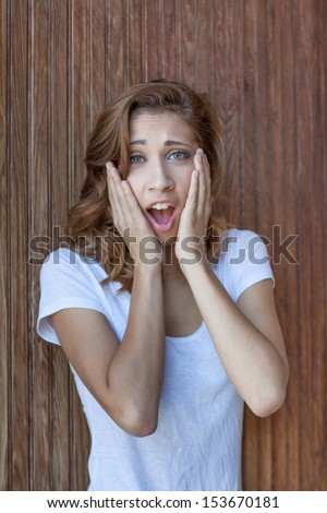 vertical orientation close up of a beautiful young woman with her hands on her face and a look of disbelief with wooden boards in the background / No Way! - stock photo