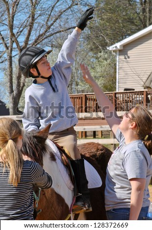vertical orientation close up of a happy boy on horseback trying to get his instructor to jump for a High Five / High Five on Horseback - stock photo