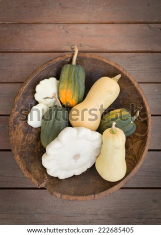 vertical orientation close up of several different types of squash, neatly arranged in a wooden bowl, with neutral background / Harvest Squash - stock photo