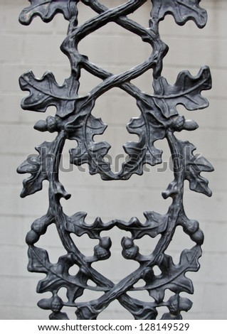 vertical orientation close up of vintage wrought iron detail with leaves, acorns and branches intertwined / Vintage Acorns - stock photo