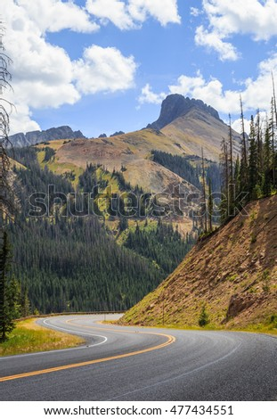 vertical orientation color image of a highway winding through the Rocky Mountains at high elevation, with copy space / Highway through the Rockies