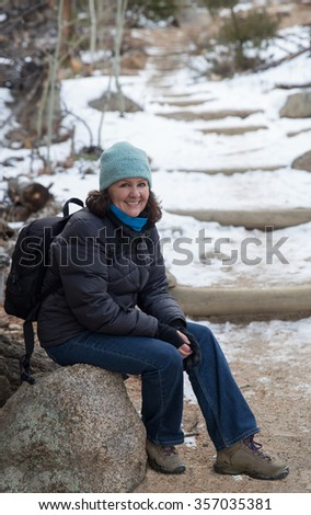 vertical orientation color image of a single woman in winter clothing, with a backpack, resting on a rock along the snowy trail / Woman Hiker in the Rocky Mountains - stock photo