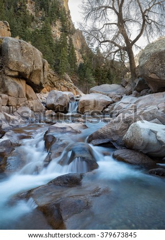 vertical orientation color image, taken with a very slow shutter speed to show the movement of water on the South St. Vrain Creek in Colorado / Serene Waterfalls - stock photo