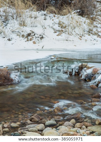 vertical orientation color image, taken with a very slow shutter speed to show the movement of water in a partly frozen stream / Ice Formations in Running Water - stock photo