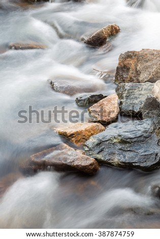 vertical orientation color image, taken with a very slow shutter speed to show the movement of water in a creek through a rocky landscape / Waterfall in Slow Motion