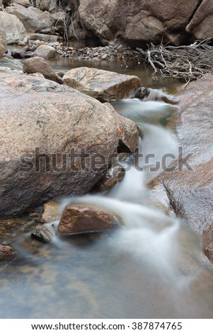 vertical orientation color image, taken with a very slow shutter speed to show the movement of water in a creek through a rocky landscape / Beautiful Winter Waterfall - stock photo