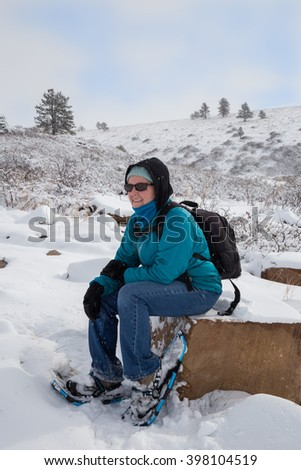 vertical orientation color image with a single, happy woman with backpack and snowshoes resting on a rock with mountains in the background/ Taking a Break from Snowshoeing - stock photo