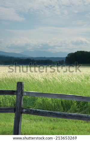 vertical orientation looking out on meadows with a wooden fence in the foreground, and mountains and sky in the background and copy space / Northern Idaho - Vertical Orientation - stock photo
