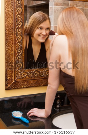 vertical orientation of a lovely, smiling, teenage girl with long hair, applying makeup with a brush as she looks in the mirror / A Happy Reflection - stock photo