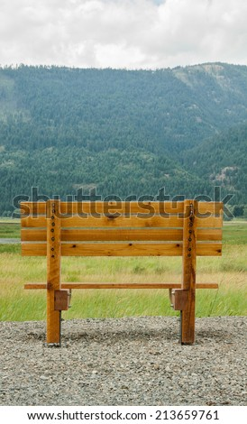 vertical orientation of a single, empty, wooden bench in the foreground, with the majestic Selkirk Mountain Range in the background, with copy space / Spectacular Northern Idaho - Vertical - stock photo