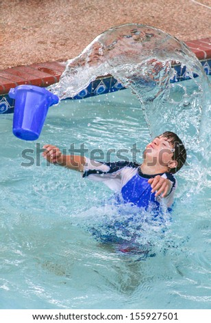 vertical orientation of boy with autism and down's syndrome outside in the pool playing with a bucket of water /  Sensory Splash Play - stock photo