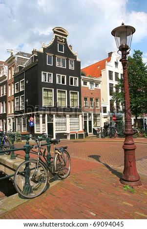 Vertical oriented image of bicycle near lamppost in front of historic house in Amsterdam, Netherlands (Holland). - stock photo