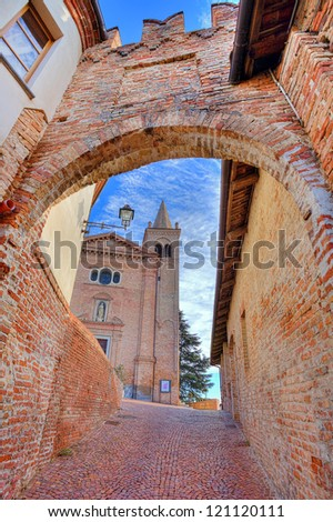 Vertical oriented image of church and medieval brick fortification wall and narrow cobbled street in town of Monticello D'Alba in Piedmont, Italy. - stock photo