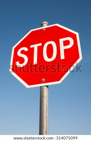 Vertical perspective of stop sign and blue sky - stock photo