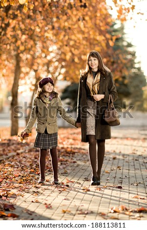 Vertical photo,  happy beautiful little girl with mather  walking in park - stock photo