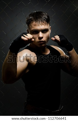 vertical photo  muscular young  guy street-fighter,  aggression look, hard light - stock photo
