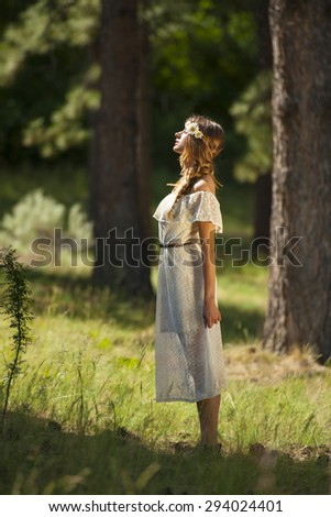 Vertical photo of beautiful young boho woman standing in forest with dramatic sunlight - stock photo