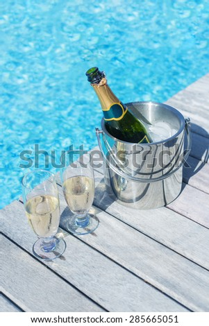 Vertical photo of champagne bottle in bucket and two glasses of champagne on the deck by the swimming pool - stock photo