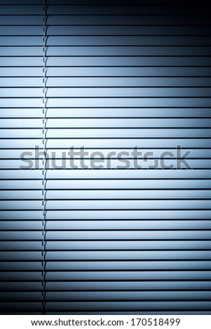 Vertical photo of closed venetian blinds or shutters under blue evening spotlight. - stock photo