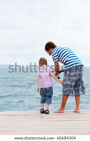 Vertical photo of father and son fishing from wooden jetty