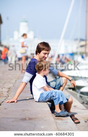Vertical photo of father and son sitting by the water in city harbor - stock photo