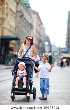 Vertical photo of mother with her son and toddler daughter in stroller walking in city center - stock photo