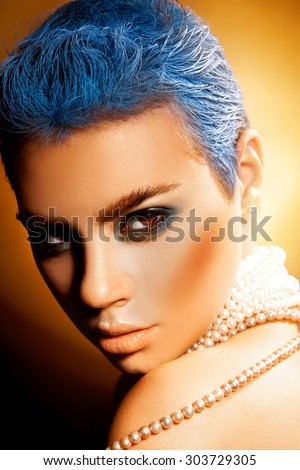 Vertical photo of sexy young woman with blue hair and green makeup. studio shot. orange background