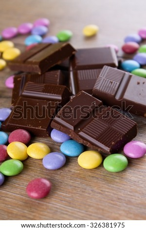 Vertical photo of small heap with dark bitter chocolate broken to pieces and several chocolate colorful coated sweets which is placed on wooden board.   - stock photo