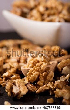 Vertical photo of spilled walnuts on black slate stone in front of white modern bowl. Few nuts are placed in wooden spoon and big one in front. - stock photo