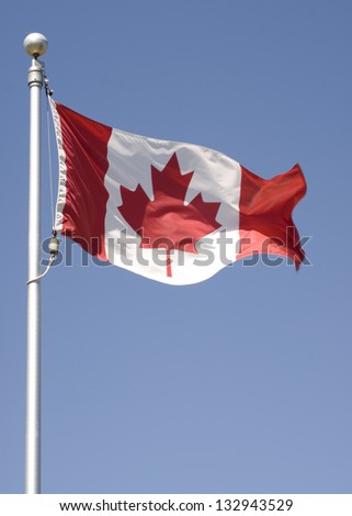 Vertical photo of the Canadian flag flying in the breeze. - stock photo