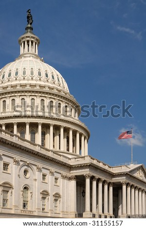 vertical photo of The Capitol, Washington DC, american flag waving, blue sky